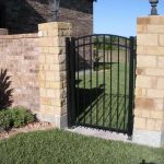 Arched Aluminum Swing Gate Set Between Brick Columns